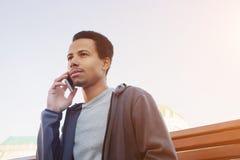Jeune homme dans l'usage de sport parlant au téléphone portable Type dehors Photo stock