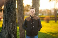 Jeune homme dans la chemise bleu-fonc? posant pour le photographe en parc photos libres de droits