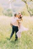 Jeune homme dans la chemise de pêche se soulevant vers le haut de sa belle amie portant la robe et la guirlande lilas Photographie stock libre de droits
