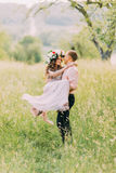 Jeune homme dans la chemise de pêche se soulevant vers le haut de sa belle amie portant la robe et la guirlande lilas Photographie stock
