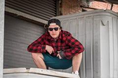 Jeune homme dans la chemise de plaid et des lunettes de soleil dans l'alle industriel de brique Images libres de droits