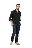 Jeune homme dans la chemise noire avec roulé vers le haut de la marche de douilles Photographie stock