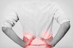Jeune homme dans la chemise occasionnelle de bureau ayant la douleur de hanche Images stock