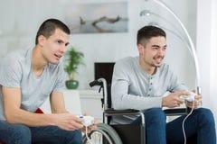 Jeune homme dans la roue jouant des jeux vidéo avec l'ami Photographie stock