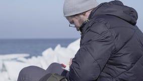Jeune homme dans la veste chaude et le chapeau se reposant sur le glacier notant ses pensées dans un petit carnet Nature ?tonnant banque de vidéos