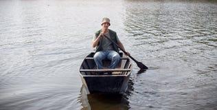 Jeune homme dans le bateau de pêche Images stock