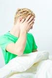 Jeune homme dans le bâti, essayant de dormir Photographie stock