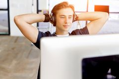 Jeune homme dans le bureau avec des écouteurs images stock