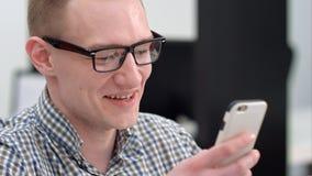 Jeune homme dans le bureau riant du message textuel sur le smartphone Photos stock