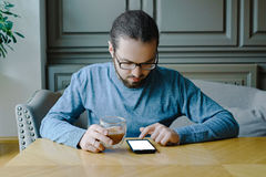 Jeune homme dans le caffe avec le smartphone tandis que coupure d'affaires Image libre de droits