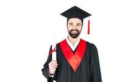 Jeune homme dans le chapeau d'obtention du diplôme tenant le diplôme et regardant l'appareil-photo Photos libres de droits