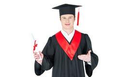 Jeune homme dans le chapeau d'obtention du diplôme tenant le diplôme sur le blanc Image stock