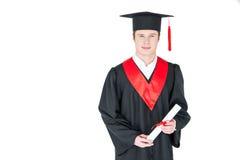 Jeune homme dans le chapeau d'obtention du diplôme tenant le diplôme sur le blanc Image libre de droits