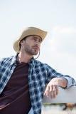 Jeune homme dans le chapeau de cowboy et la chemise à carreaux semblant partis et se penchant sur la barrière au ranch Photos libres de droits