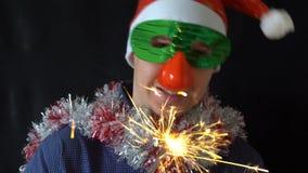 Jeune homme dans le chapeau de Noël et masque tenant un cierge magique brûlant banque de vidéos