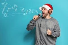Jeune homme dans le chapeau de Santa chantant dans le microphone sur le fond de couleur image stock