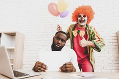 Jeune homme dans le clown Costume avec Baloons dans le bureau photo stock