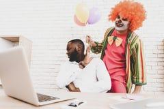 Jeune homme dans le clown Costume avec Baloons dans le bureau images libres de droits