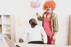 Jeune homme dans le clown Costume avec Baloons dans le bureau photos libres de droits