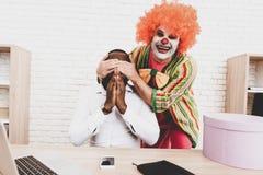 Jeune homme dans le clown Costume sur la réunion dans le bureau image libre de droits