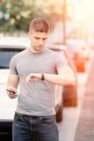 Jeune homme dans le contexte urbain avec le téléphone portable Image libre de droits