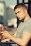 Jeune homme dans le contexte urbain avec le téléphone portable Images libres de droits