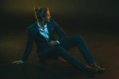 Jeune homme dans le costume élégant se reposant sur la planche à roulettes Photographie stock