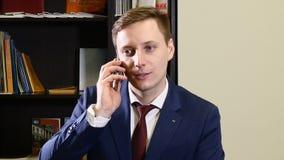 Jeune homme dans le costume dans le bureau parlant au téléphone Homme futé invitant le téléphone portable à l'intérieur Jeune hom banque de vidéos