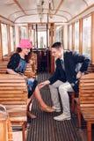 Jeune homme dans le costume dans le wagon de train avec le regard de sourire de femme à Photographie stock