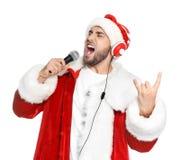 Jeune homme dans le costume de Santa chantant dans le microphone photographie stock libre de droits