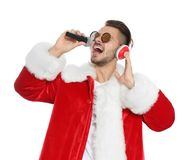 Jeune homme dans le costume de Santa chantant dans le microphone sur le fond blanc images libres de droits