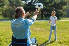 Jeune homme dans le fauteuil roulant passant une boule à sa fille Photos libres de droits