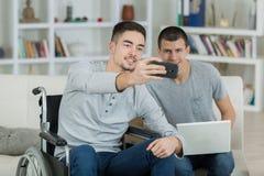 Jeune homme dans le fauteuil roulant prenant le selfie avec l'ami Photographie stock libre de droits