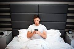 Jeune homme dans le lit ce matin Il tiennent le téléphone Regard de type à lui Homme sérieux et concentré bedtime images libres de droits