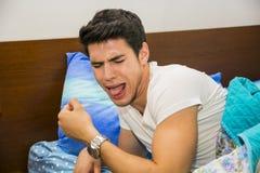 Jeune homme dans le lit dégoûté par le sirop de toux Images libres de droits