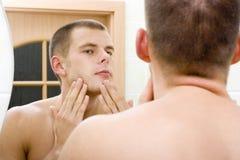 Jeune homme dans le miroir de la salle de bains après rasage Photo stock