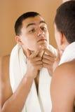 Jeune homme dans le miroir de la salle de bains nettoyant sa peau Images stock