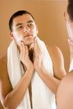 Jeune homme dans le miroir de la salle de bains utilisant la crème Images libres de droits