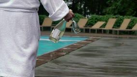 Jeune homme dans le peignoir marchant avec la bouteille de champagne près de la piscine banque de vidéos