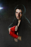 Jeune homme dans le pullover de hoodie de boxe avec le capot sur la main de port principale et prêt enveloppé par poignet pour la Image libre de droits
