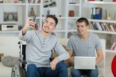 Jeune homme dans le selfie parlant de fauteuil roulant avec l'ami Photos libres de droits