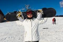 Jeune homme dans le ski-costume tenant et tenant le sien surf des neiges sur le sien Photo libre de droits