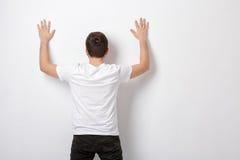 Jeune homme dans le T-shirt blanc avec des mains vers le haut de mur proche, vue arrière d Photos libres de droits