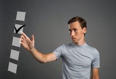 Jeune homme dans le T-shirt vérifiant la boîte de liste de contrôle Fond gris Photo stock