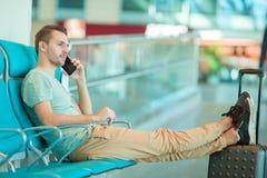 Jeune homme dans un avion de attente de vol de salon d'aéroport Homme caucasien avec le smartphone d'intérieur Photographie stock