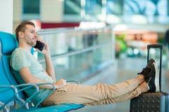Jeune homme dans un avion de attente de vol de salon d'aéroport Homme caucasien avec le smartphone d'intérieur Image libre de droits