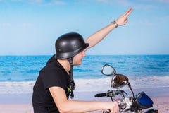 Jeune homme dans un casque saluant comme il monte un vélo Images stock