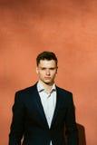 jeune homme dans un costume noir sur un fond d'un mur orange Photographie stock libre de droits