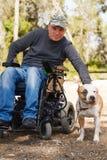 Jeune homme dans un fauteuil roulant avec son chien fidèle. Photographie stock