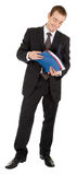 Jeune homme dans un procès noir d'affaires avec un dépliant i Photographie stock libre de droits